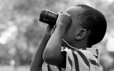 Foto em preto e branco mostra menino com binóculos