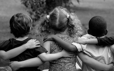 Foto em preto e branco de três crianças abraçadas representa a proteção aos direitos dessa população
