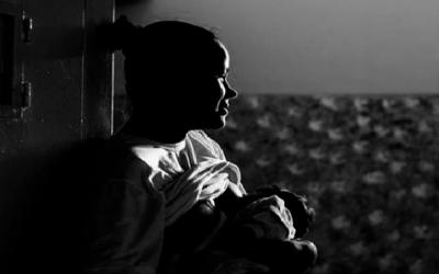 Foto em preto e branco mostra mãe em privação de liberdade amamentando bebê