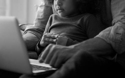 Foto em preto e branco mostra pai e criança mexendo em notebook