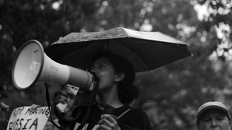 Foto em preto e branco de mulher com megafone e um guarda chuva
