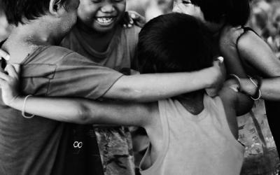Foto em preto e branco mostra quatro crianças se abraçando sorridentes