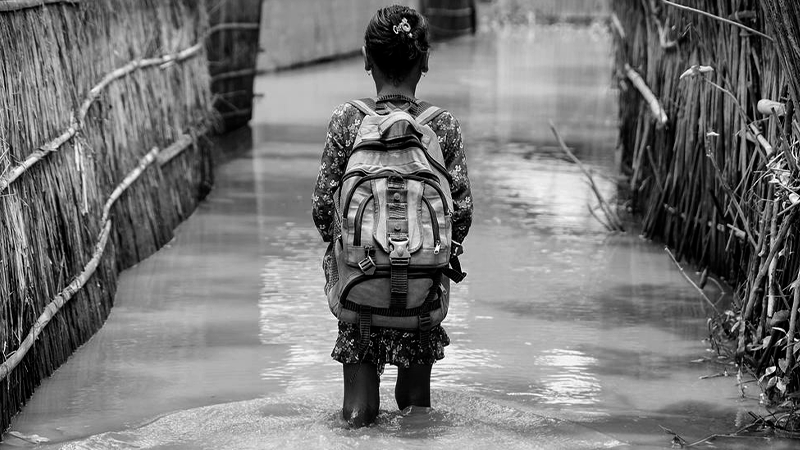 Foto em preto e branco de criança indígena com mochila em caminho alagado