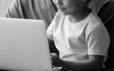 Foto em preto e branco mostra criança mexendo em notebook