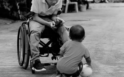 Foto em preto e branco mostra criança em cadeira de rodas brincando com bebê