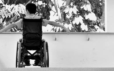 Foto em preto e branco mostra criança em cadeira de rodas com os braços abertos, representa a educação inclusiva