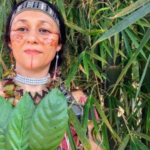 Foto mostra Cristine Takuá, com o rosto pintado, segurando algumas folhas