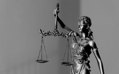 Foto em preto e branco mostra estátua da justiça segurando balanças. Representa o julgamento da lei que autoriza o porte de armas para agentes socioeducativos