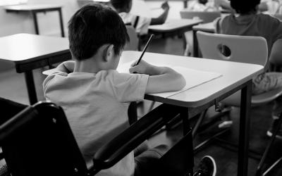 Foto em preto e branco mostra criança na escola escrevendo. Representa a necessidade da comunidade escolar estar atenta `às crianças vítimas de violência na volta às aulas