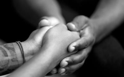 Foto em preto e branco mostra adulto segurando mão de adolescente