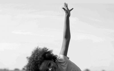 Foto em preto e branco mostra criança feliz com os braços erguidos. Representa comemoração pela vitória do Conanda