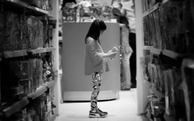 Foto em preto e branca mostra menina no corredor de salgadinhos do supermercado. Representa a disposição do marco legal contra à pressão consumista e comunicação mercadológica direcionada a essa população