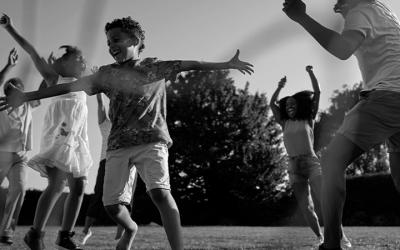 Foto em preto e branco mostra várias crianças sorridentes comemorando. Representa celebração pelo aniversário do Marco Legal