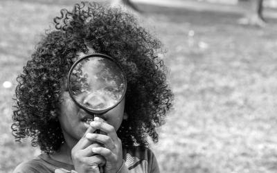 Foto em preto e branco mostra criança brincando com lupa, representando o Conanda procurando por organizações para participarem da eleição